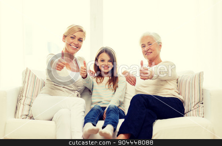 smiling family at home stock photo, family, happiness, generation and people concept - smiling mother, daughter and grandmother sitting on couch at home by Syda Productions