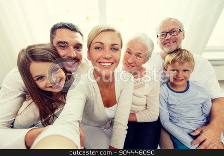 happy family making selfie at home stock photo, family, happiness, generation and people concept - happy family sitting on couch and making self portrait with camera or smartphone at home by Syda Productions