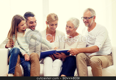 happy family with book or photo album at home stock photo, family, happiness, generation and people concept - happy family with book or photo album sitting on couch at home by Syda Productions