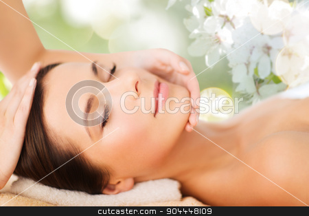 beautiful woman in spa salon having facial massage stock photo, spa, beauty, people and body care concept - beautiful woman getting face treatment over green natural background by Syda Productions