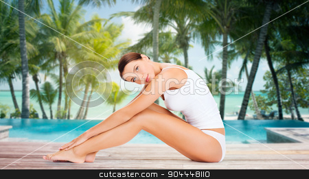 beautiful woman touching her legs over beach stock photo, people, beauty, spa, travel and resort concept - beautiful woman in cotton underwear touching her legs over swimming pool on beach with palms background by Syda Productions