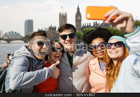 smiling friends taking selfie with smartphone stock photo, tourism, travel, people, leisure and technology concept - group of smiling teenage friends taking selfie with smartphone over houses of parliament and thames river in london background by Syda Productions