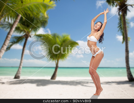 happy young woman in white bikini swimsuit dancing stock photo, people, travel, swimwear and summer concept - happy young woman posing in white bikini swimsuit dancing with raised hands over tropical beach with palm trees background by Syda Productions