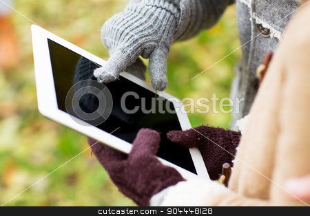couple hands in gloves with tablet pc outdoors stock photo, technology, advertisement and people concept - close up of couple hands in autumn gloves holding tablet pc computer outdoors by Syda Productions