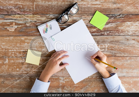 close up of hands with papers and eyeglasses stock photo, business, education and people concept - close up of female hands with papers, stickers and eyeglasses on table by Syda Productions