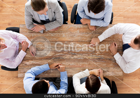 close up of business team sitting at table stock photo, business, people and team work concept - close up of creative team sitting at table and pointing finger to something in office by Syda Productions
