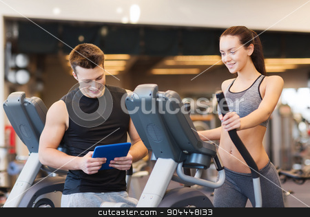 woman with trainer exercising on stepper in gym stock photo, sport, fitness, lifestyle, technology and people concept - woman with trainer exercising on stepper in gym by Syda Productions