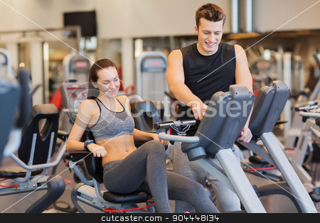 happy woman with trainer on exercise bike in gym stock photo, sport, fitness, lifestyle, technology and people concept - happy woman with trainer working out on exercise bike in gym by Syda Productions