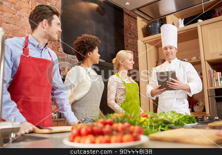 happy friends with tablet pc in kitchen stock photo, cooking class, culinary, food, technology and people concept - happy friends with tablet pc in kitchen by Syda Productions