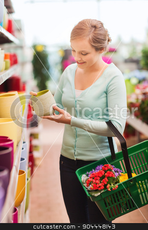 woman with shopping basket choosing flowerpot stock photo, people, gardening, shopping, sale and consumerism concept - happy woman with basket buying flowers and choosing flowerpot at flower shop by Syda Productions