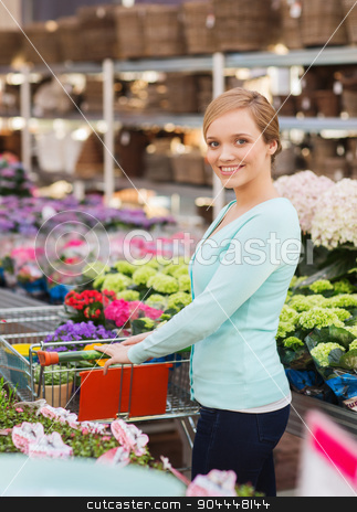 happy woman with shopping trollye buying flowers stock photo, people, gardening, shopping, sale and consumerism concept - happy woman with trolley buying flowers at greenhouse or shop by Syda Productions