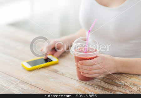 close up of woman with smartphone and smoothie stock photo, healthy eating, diet, technology and people concept - close up of woman with smartphone and cup of smoothie sitting at table by Syda Productions