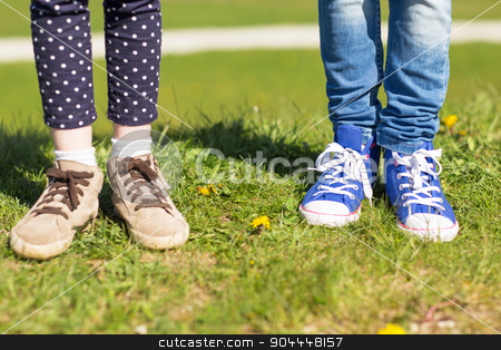 close up of kids legs in shoes on grass outdoors stock photo, people, children, friends and friendship concept - close up of kids legs in shoes on grass outdoors by Syda Productions