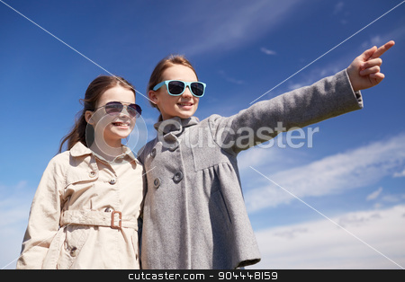 happy little girls hugging and pointing finger stock photo, people, children, friends and friendship concept -happy little girls in sunglasses hugging and pointing finger outdoors by Syda Productions