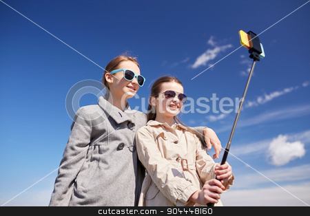 happy girls with smartphone selfie stick stock photo, people, children, friends and friendsip concept - happy girls taking picture with smartphone on selfie stick outdoors by Syda Productions