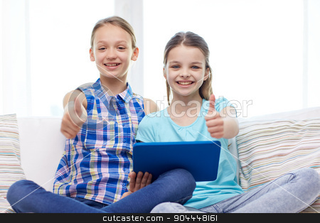 happy girls with tablet pc and showing thumbs up stock photo, people, children, gesture, friends and friendship concept - happy little girls with tablet pc computer sitting on sofa and showing thumbs up at home by Syda Productions