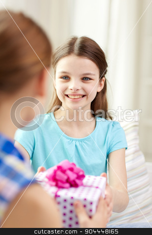 happy little girls with birthday present at home stock photo, people, children, holidays, friends and friendship concept - happy little girls with birthday present sitting on sofa at home by Syda Productions