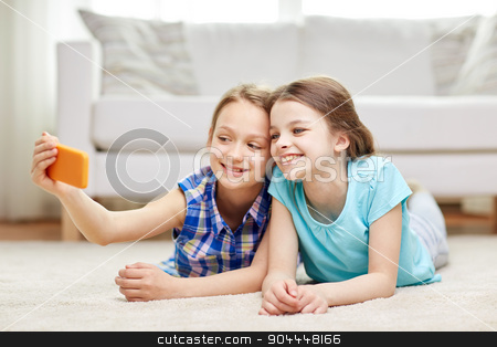 happy girls with smartphone taking selfie at home stock photo, people, children, technology, friends and friendship concept - happy little girls lying on floor and taking selfie with smartphone at home by Syda Productions