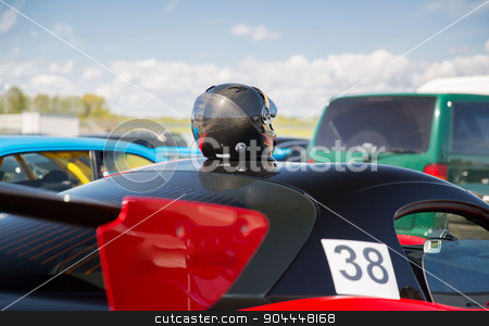close up of car with helmet on roof top stock photo, transportation, high speeds, racing and road concept - close up of car on autodrome or parking with helmet on roof top from back by Syda Productions
