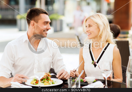 happy couple eating dinner at restaurant terrace stock photo, love, date, people, holidays and relations concept - happy couple eating salad for dinner at cafe or restaurant terrace by Syda Productions