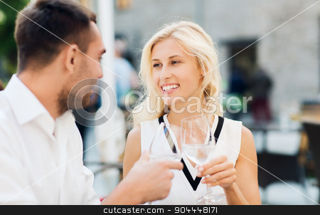 smiling couple drinking champagne at cafe stock photo, love, dating, people and holidays concept - smiling couple wearing sunglasses drinking champagne and looking to each other at cafe by Syda Productions
