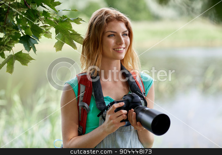 happy woman with backpack and camera outdoors stock photo, adventure, travel, tourism, hike and people concept - happy young woman with backpack and camera photographing outdoors by Syda Productions