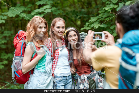 friends with backpack photographing by smartphone stock photo, travel, tourism, hike, technology and people concept - group of smiling friends walking with backpacks taking picture by smartphone in woods by Syda Productions