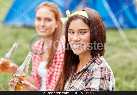 happy young women with tent and drinks at campsite stock photo, camping, travel, tourism, hike and people concept - happy young women with glass bottles drinking cider or beer at campsite by Syda Productions