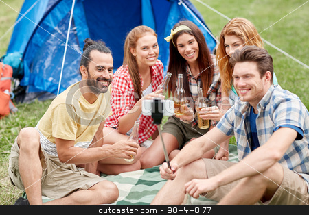 happy friends taking selfie by smartphone at camp stock photo, camping, travel, tourism, hike and people concept - happy friends with glass bottles drinking cider or beer and taking picture by smartphone on selfie stick at camping by Syda Productions