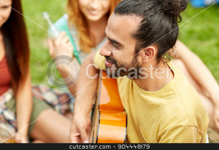 happy man with friends playing guitar at camping stock photo, travel, tourism, hike, leisure and people concept - happy man with friends playing guitar at camping by Syda Productions