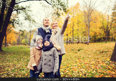 happy family in autumn park stock photo, family, childhood, season, gesture and people concept - happy family pointing finger in autumn park by Syda Productions
