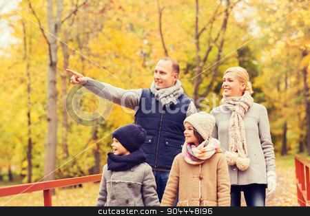 happy family in autumn park stock photo, family, childhood, season and people concept - happy family pointing finger in autumn park by Syda Productions