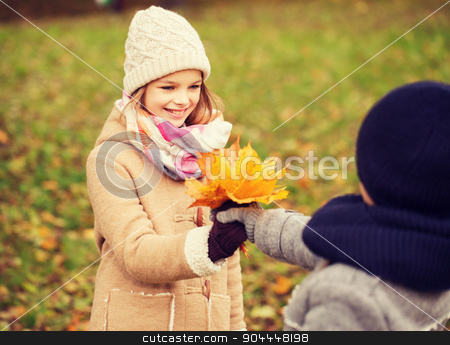 smiling children in autumn park stock photo, childhood, season and people concept - smiling little girl and boy with autumn leaves in park by Syda Productions