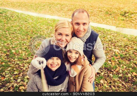 happy family with selfie stick in autumn park stock photo, family, childhood, season, technology and people concept - happy family photographing with selfie stick in autumn park by Syda Productions