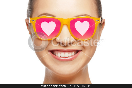 smiling teenage girl in pink sunglasses stock photo, love, happiness, valentines day, face expressions and people concept - portrait of smiling teenage girl in pink sunglasses with hearts by Syda Productions