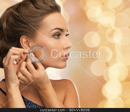 close up of woman wearing earrings stock photo, people, holidays, christmas and glamour concept - close up of beautiful woman wearing earrings over beige lights background by Syda Productions