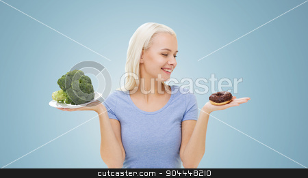 smiling woman with broccoli and donut stock photo, healthy eating, junk food, diet and choice people concept - smiling woman choosing between broccoli and donut over blue background by Syda Productions