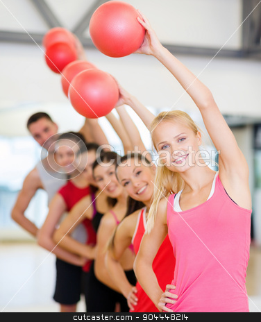 group of smiling people working out with ball stock photo, fitness, sport, training, gym and lifestyle concept - group of smiling people working out with stability balls in the gym by Syda Productions