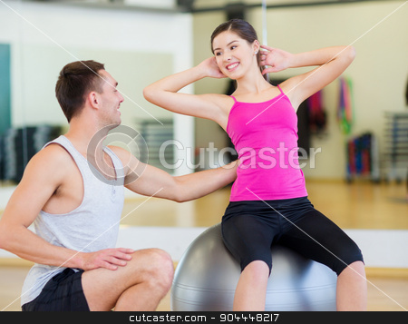 male trainer with woman doing crunches on the ball stock photo, fitness, sport, training, gym and lifestyle concept - male trainer with woman doing crunches on the ball by Syda Productions