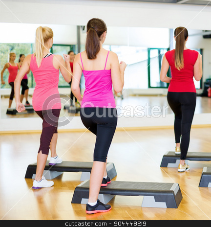 group of smiling people doing aerobics stock photo, fitness, sport, training, gym and lifestyle concept - group of smiling people doing aerobic by Syda Productions