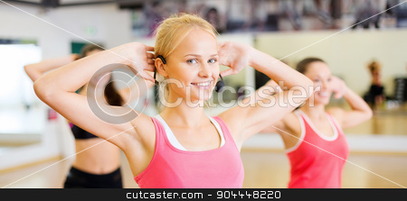 group of smiling people exercising in the gym stock photo, fitness, sport, training, gym and lifestyle concept - group of smiling people with trainer exercising in the gym by Syda Productions