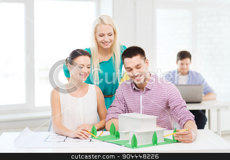 smiling architects working in office stock photo, startup, education, architecture and office concept - smiling architects with house model and blueprint working in office by Syda Productions