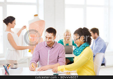 smiling fashion designers working in office stock photo, startup, education, fashion and office concept - smiling designers drawing sketches and adjusting dress on mannequin in office by Syda Productions