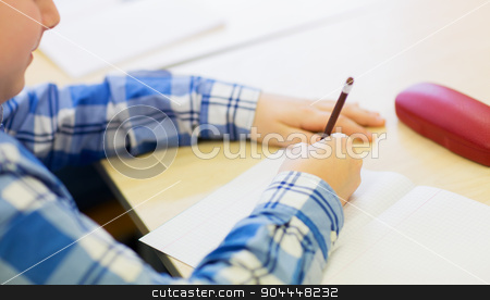 close up of schoolboy writing test at school stock photo, education, elementary school, learning and people concept - close up of little schoolboy with notebook and pencil writing test at school by Syda Productions