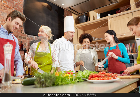 happy friends and chef cook cooking in kitchen stock photo, cooking class, culinary, food and people concept - happy group of friends with male chef cook cooking and talking in kitchen by Syda Productions