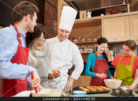 happy friends and chef cook baking in kitchen stock photo, cooking class, culinary, bakery, food and people concept - happy group of friends and male chef cook baking in kitchen by Syda Productions
