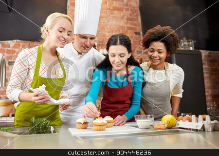 happy women and chef cook baking in kitchen stock photo, cooking class, culinary, bakery, food and people concept - happy group of women and male chef cook baking in kitchen by Syda Productions