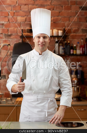 happy male chef cook in kitchen with knife stock photo, cooking, kitchenware and people concept - happy male chef cook with knife in restaurant kitchen by Syda Productions