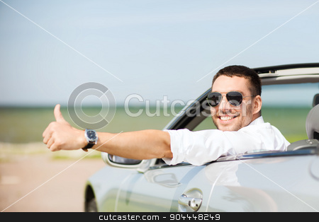 happy man driving car and showing thumbs up stock photo, auto business, transport, leisure and people concept - happy man driving cabriolet car and showing thumbs up by Syda Productions