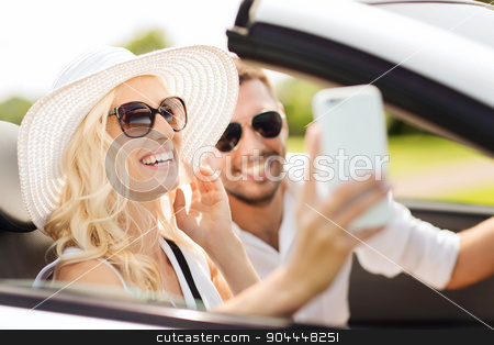 happy couple in car taking selfie with smartphone stock photo, road trip, leisure, couple, technology and people concept - happy man and woman driving in cabriolet car and taking selfie with smartphone by Syda Productions
